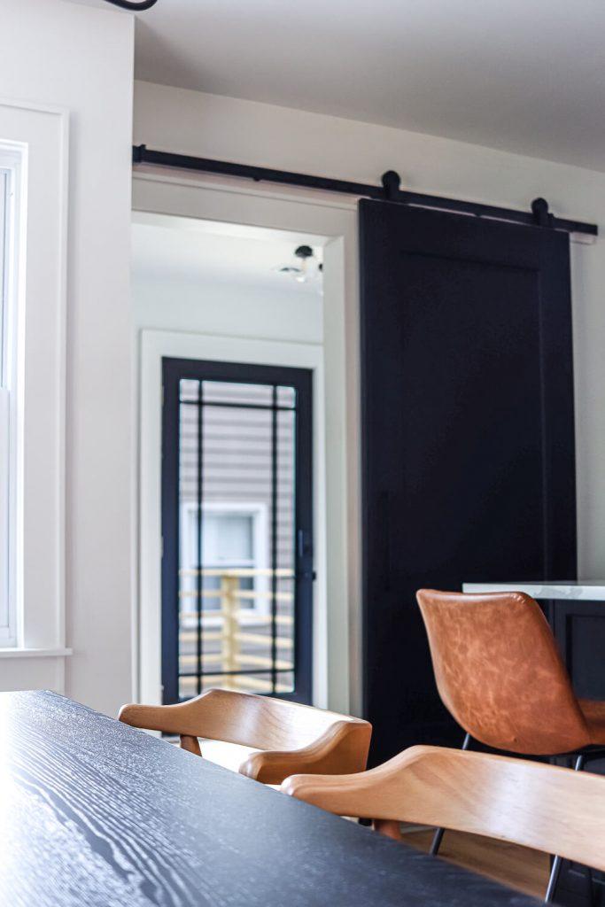 black barn door open to see black glass door
