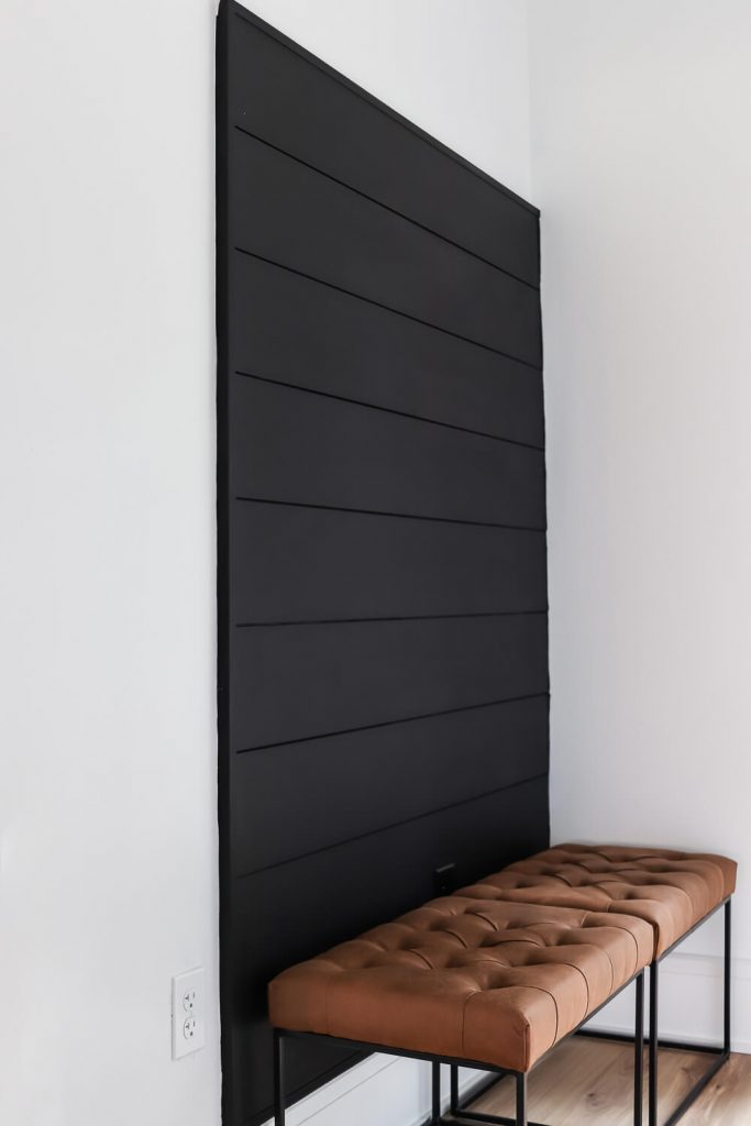 Sherwin Williams Tricorn Black shiplap accent wall with leather stools in front