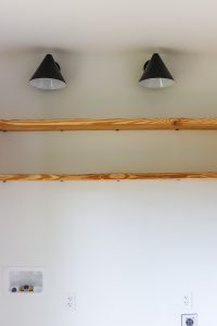 open wood shelves with 2 black sconces on white wall