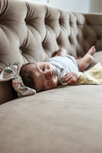 newborn girl sleeping in headband on brown tufted couch