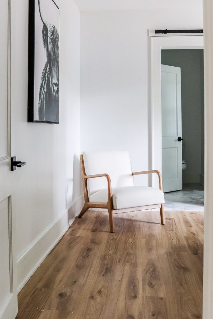 white oak LVP floors with white walls and bull painting on wall