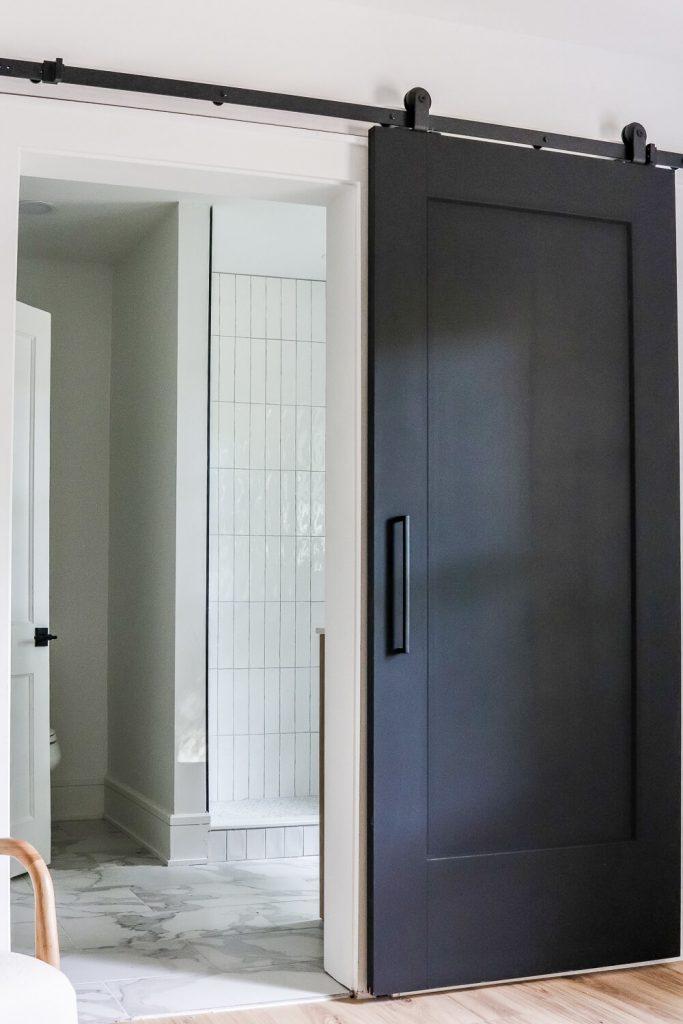 black barn door open to see primary bathroom
