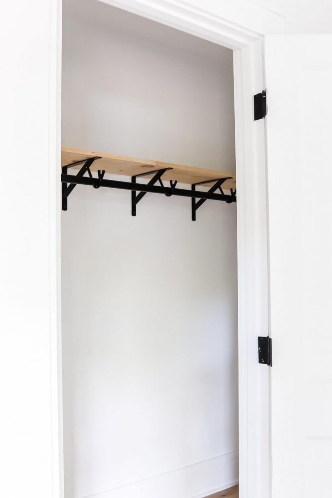 primary closet with wood shelves and black hanging closet rodf
