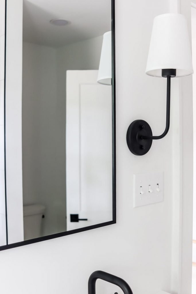black sconce with white pendant light and black frame mirror