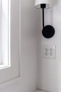 closeup of white trim and black sconce with white shade