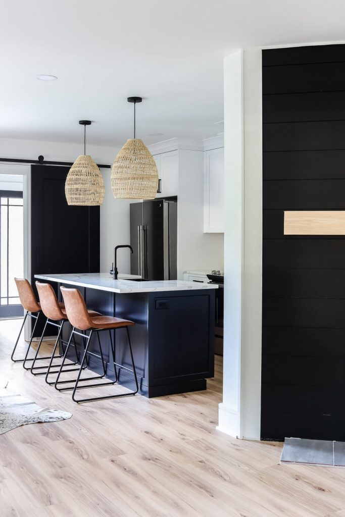 view into kitchen with black island and rattan pendants and black shiplap accent firewall with wood mantle