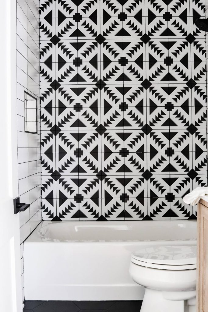 black and white patterned tile with wood vanity