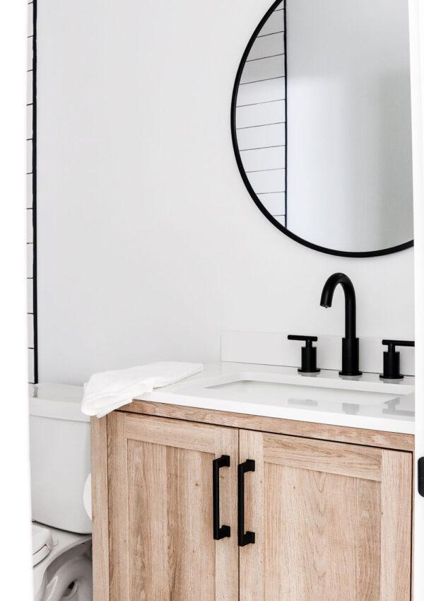 whitewashed wood vanity with black hardware and black mirror