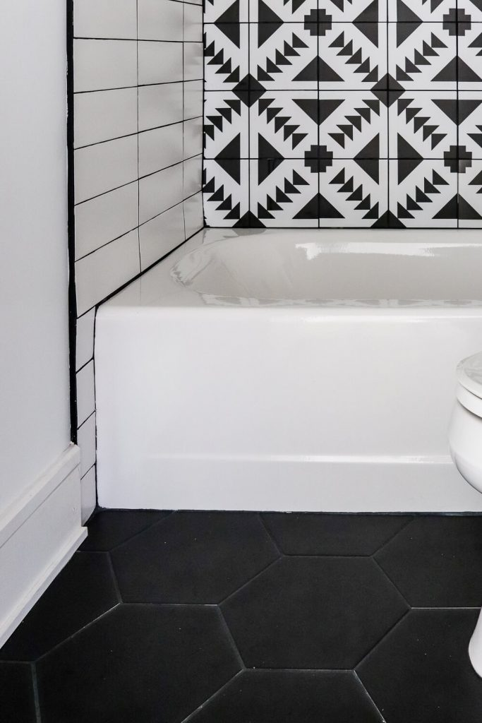 black and white patterned tile in the bathroom with white subway tile and black hexagon tile on the floor