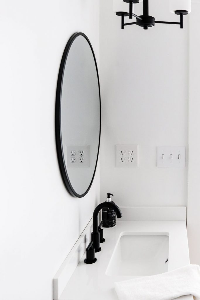 black round mirror with black pendant light and black sink fixtures