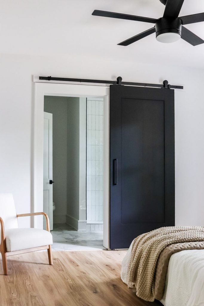 black barn door with white and wood sitting chair in bedroom and light wood floors looking into a primary bathroom