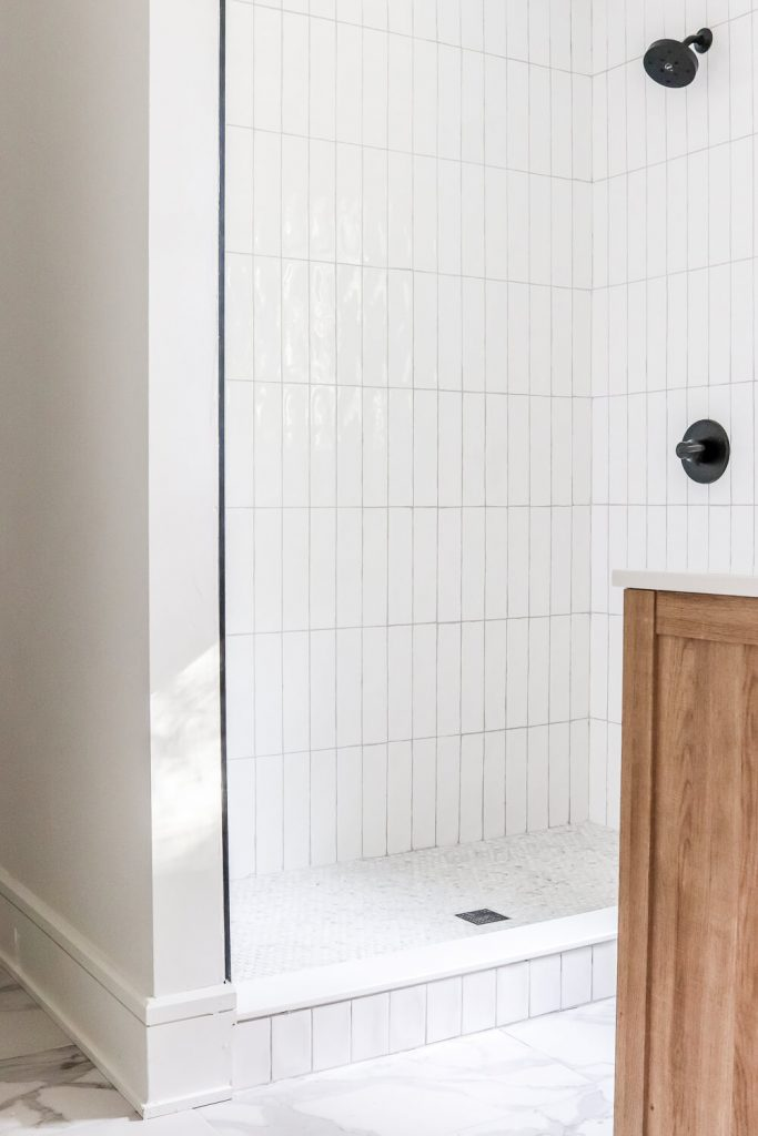 white beveled subway tile with marble look tile on the floor and marble penny tile in the shower pan and whitewashed wood vanity