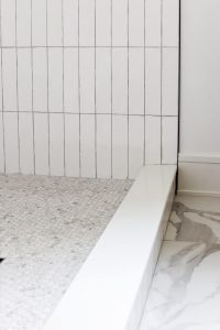 white beveled subway tile with marble look tile on the floor and marble penny tile in the shower pan