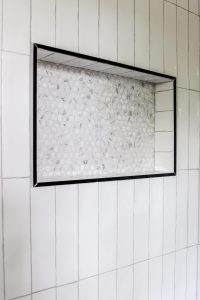 white subway tile with marble look penny tile in the shower niche