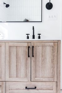 whitewashed wood vanity with black fixtures and black handles