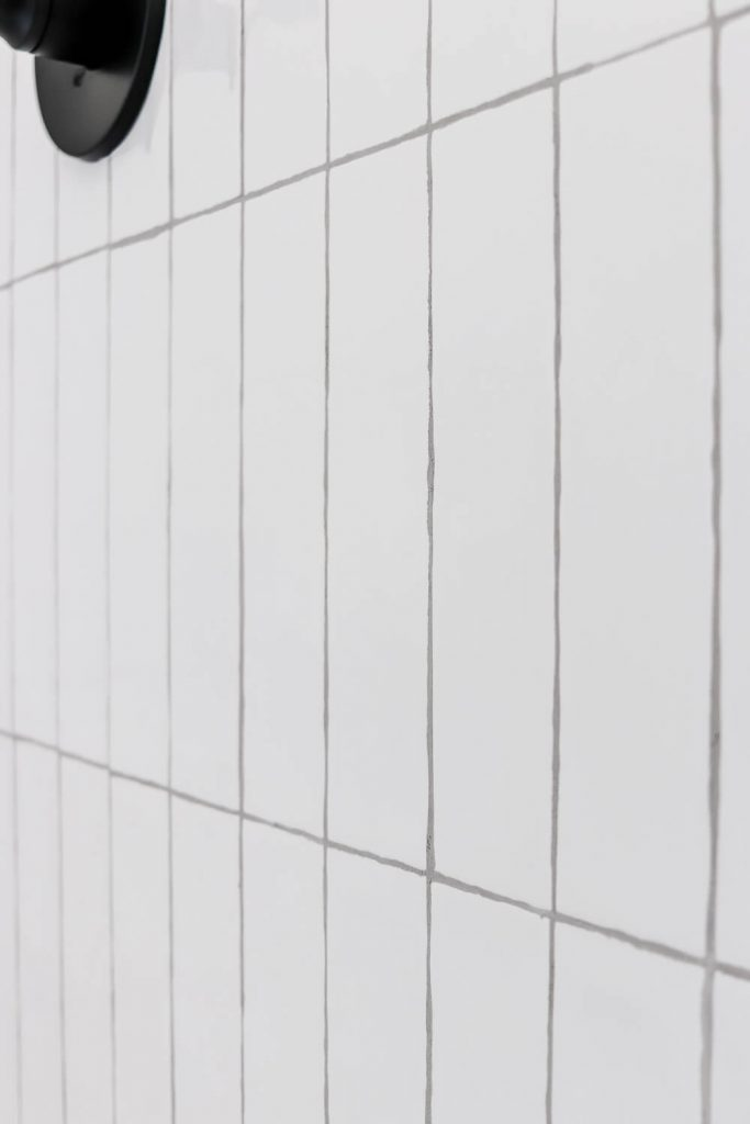 closeup of white beveled subway tile with gray grout