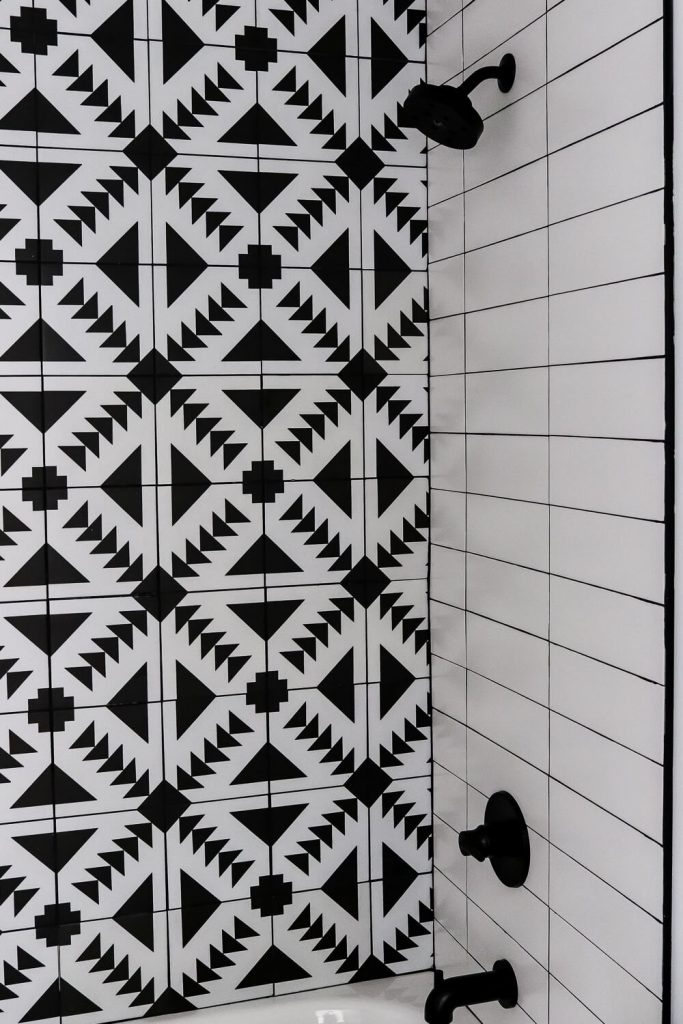 black and white patterned tile and white subway tile in a small bathroom with black shower fixtures