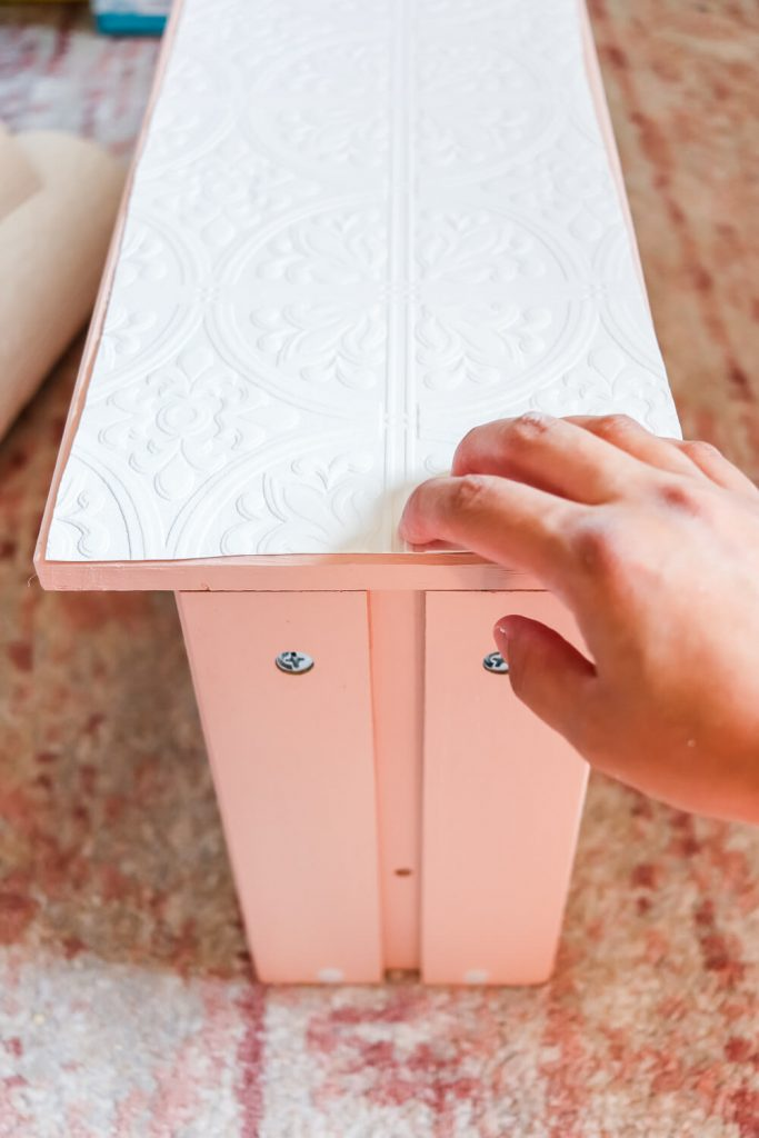 woman's hand on pink Ikea Rast drawer holding paintable wallpaper