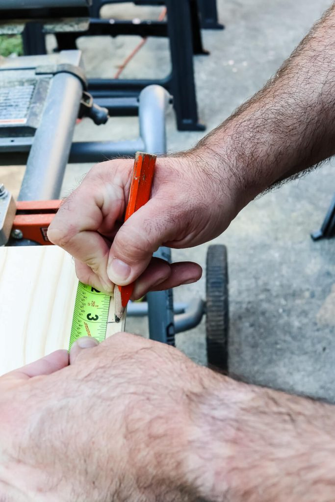 man's hand on saw using tape measure to measure wood