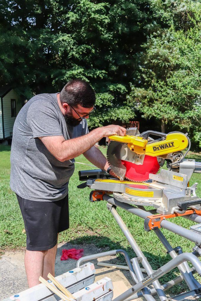 man in gray shirt cutting wood with Dewalt miter saw