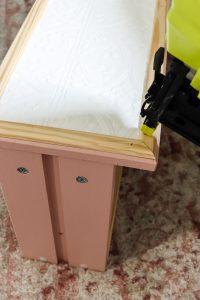 Ryobi nail gun on edge of Ikea rast dresser with paintable wallpaper