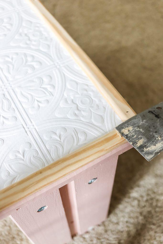 spackle knife spreading wood filler on millwork trim attached to Ikea rast dresser drawer