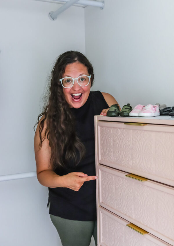 woman with blank tank top and curly hair pointing at pink Ikea Rast dresesr