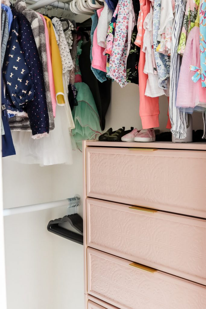 closeup of baby clothes and girl clothes in shared nursery kids closet
