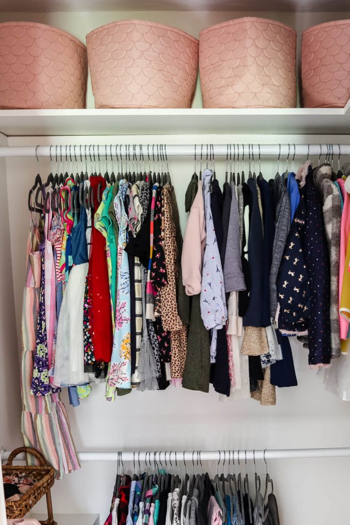 girls clothes hanging in a closet with white walls and a white wood shelf and pink storage baskets on the top