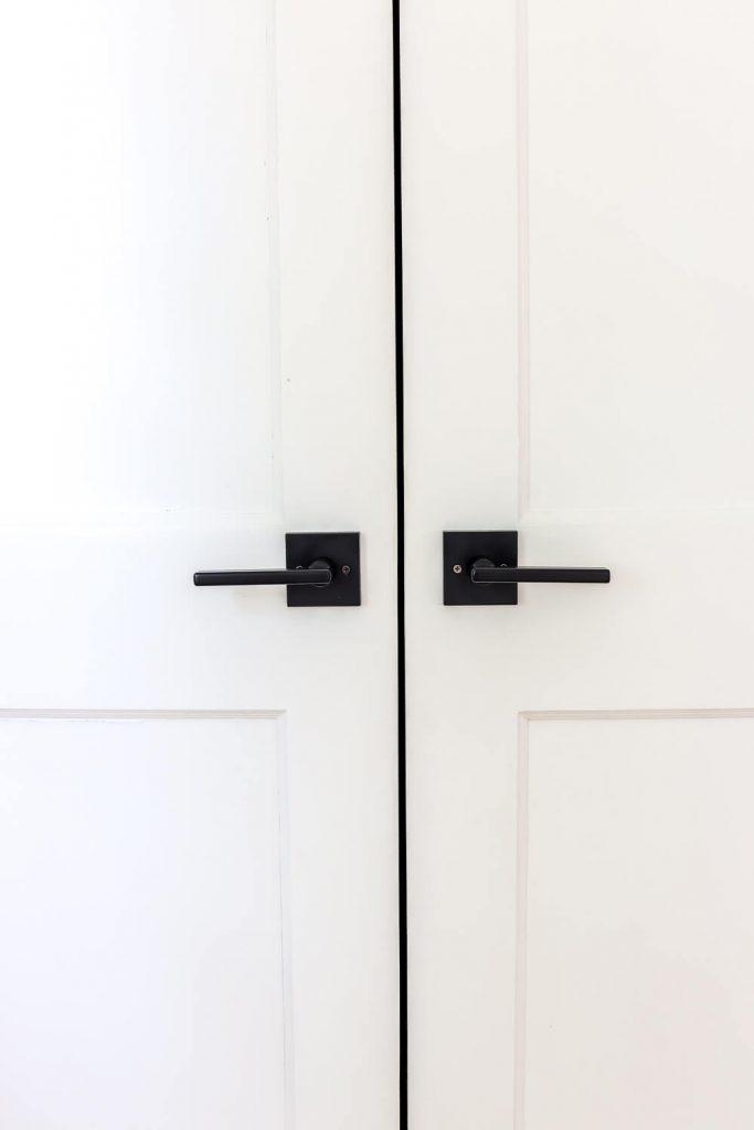 closeup of matte black Kwikset halifax door handle on white door
