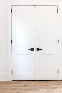 modern black door hardware on white door