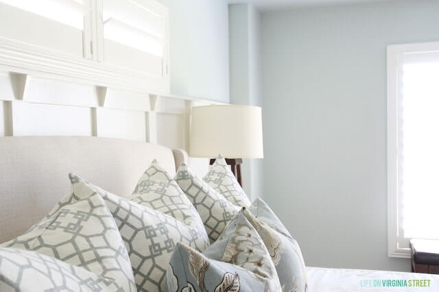 Detailed shot of pillows on the bed with Sherwin Williams Sea Salt on the wall
