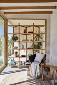 Japandi style sunroom with open wood shelves and wood chair