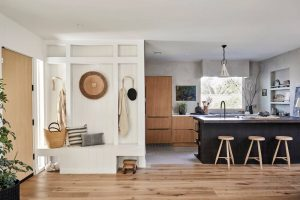 Japandi style designed view into kitchen with white built in mudroom shelves and seating