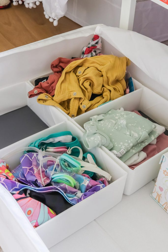 Ikea underbed storage with girls' clothes in them