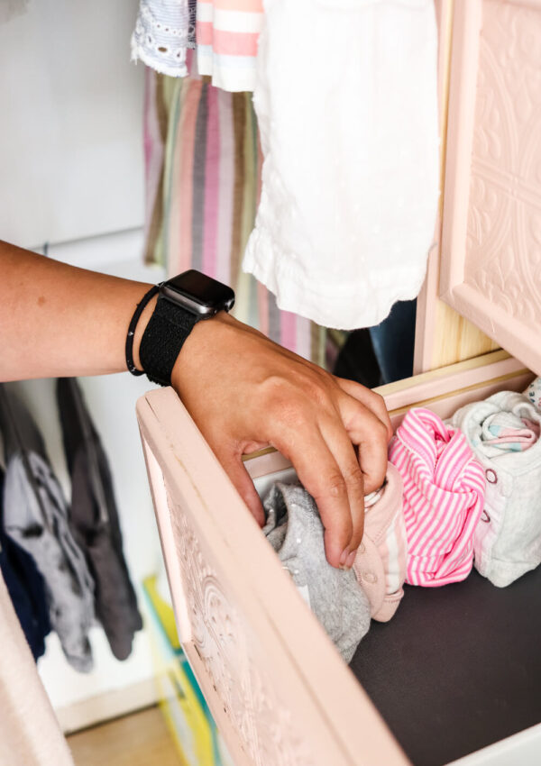 woman's hand holding rolled onesie putting it in the drawer