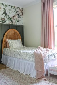 gold dot bedding with white crib sheet and vintage headboard against green nursery accent wall