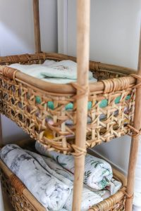 burp cloths and rolled up swaddle blankets in rattan storage