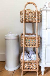 3 tier rattan storage next to white Ubi diaper pail and white changing table