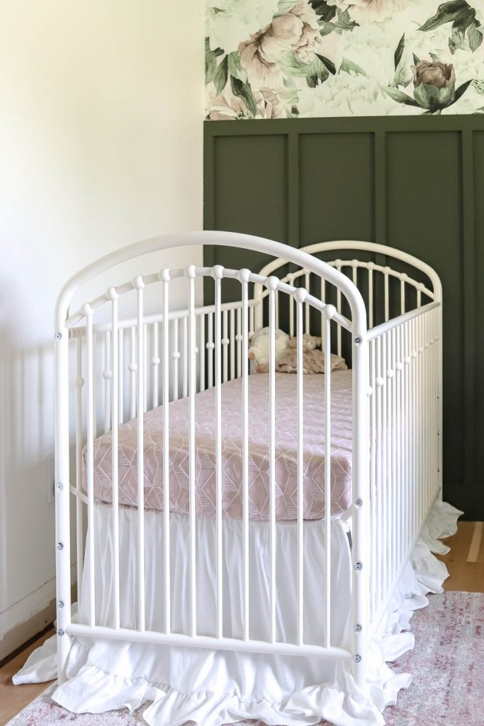 white metal crib against a dark green feature wall in nursery