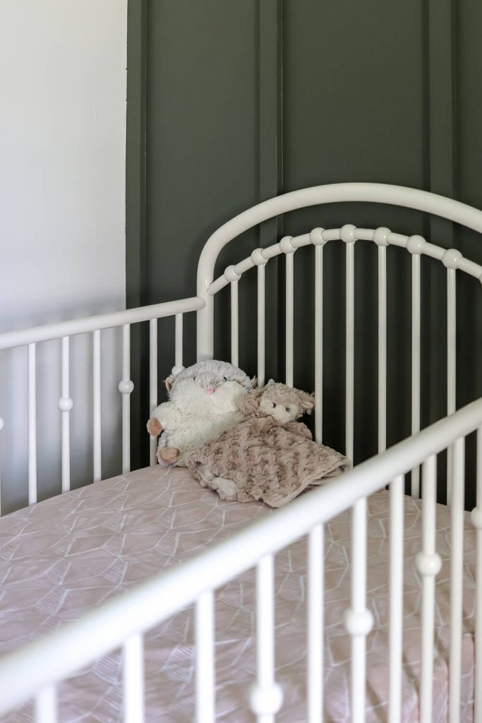 white metal crib against a dark green feature wall in nursery with lovey and hamster Warmies in crib
