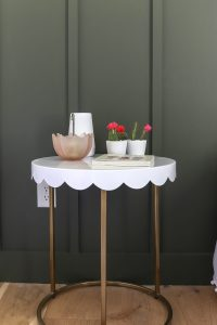white metal side table with gold legs and cactus plants on it