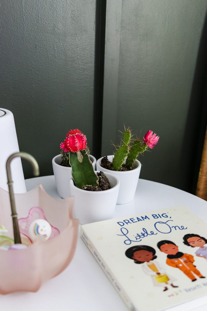 dream big little one book on white table and hunter green wall