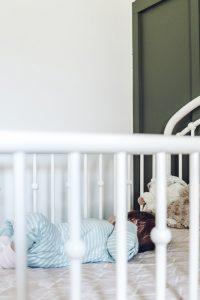 white metal crib with little girl sleeping