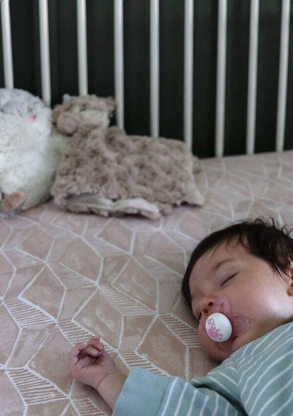 white metal crib with little girl sleeping inside