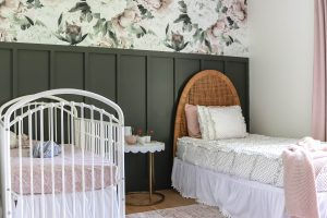 shared girls room with floral and hunter green feature wall with white metal crib and vintage woven headboard