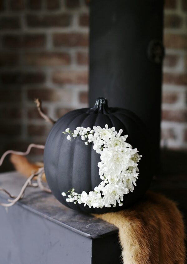 pumpkin painted black with flowers in the shape of a moon on it