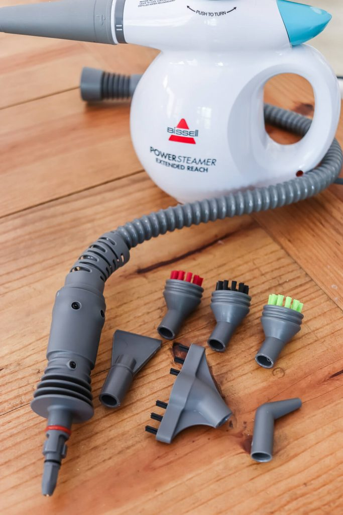 Bissell Power steamer extended reach with attachments on wood table