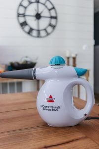 Bissell powersteamer sitting on a table with a white shiplap wall and clock in the background