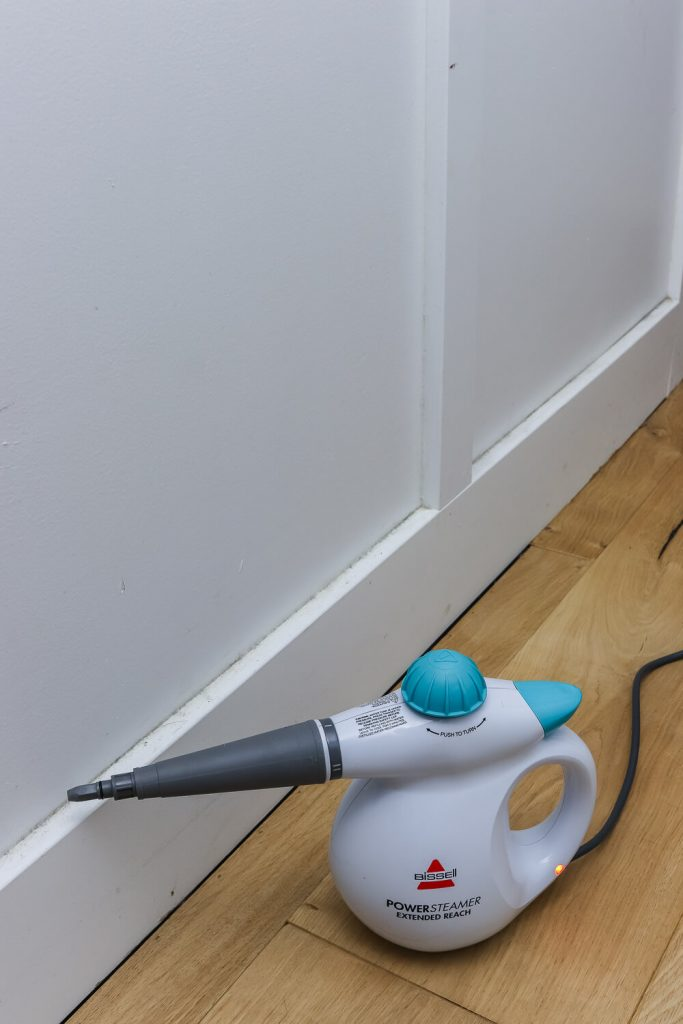 bissell handheld powersteamer in front of white baseboards